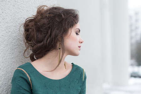 Romantic Caucasian Woman in Green Dress over White Wall outside  Solitude