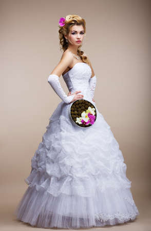 Wedding. Newlywed in White Dress holding Special Bouquet of Flowers photo