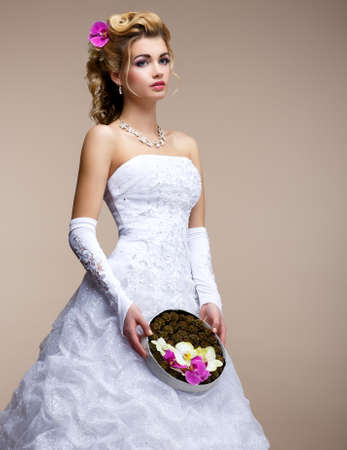 Marriage. Fashionable Bride Blonde in Bridal White Dress and Unusual Bouquet of Flowers photo