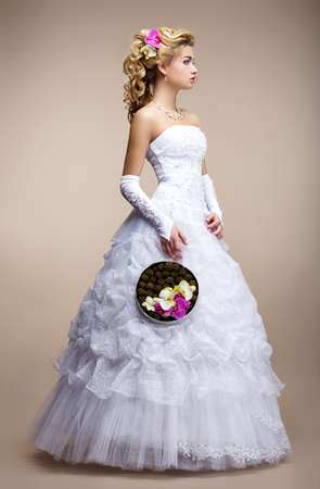 Wedding Style. Bride wearing White Dress and Gloves. Trendy Bouquet of Flowers photo