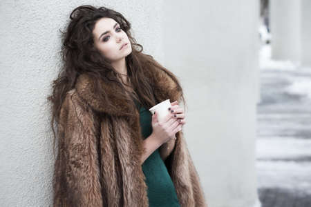 outwear: Breaktime. Attractive Thoughtful Woman holding Coffee Cup and Relaxing
