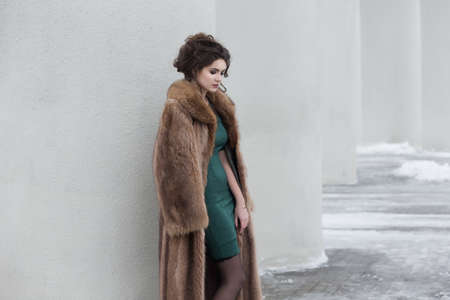 Glamour. Beauty Thoughtful Woman over White Wall in Wool Outwear dreaming photo