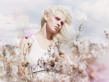 Blossom  Beauty Blonde in Windy Field with Flowers  Nature  Springtime photo