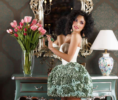 commode: Beautiful Glamorous Woman in Retro Interior with Vase of Flowers  Reflection Stock Photo