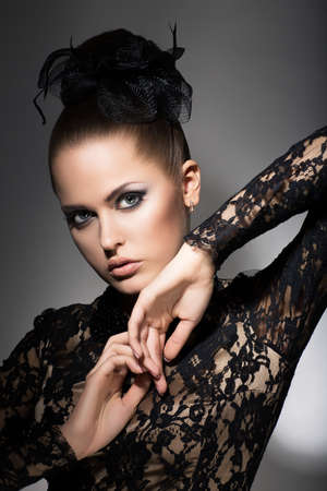 sophistication: Glamor. Luxurious Woman in Black Dress and Bow. Sophistication Stock Photo