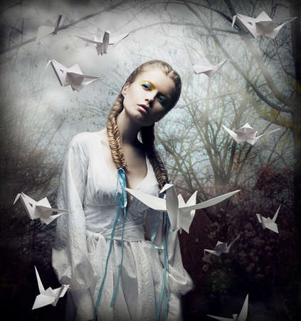 Imagination. Romantic Blonde with Hovering Origami Birds in Spooky Forest. Magic photo