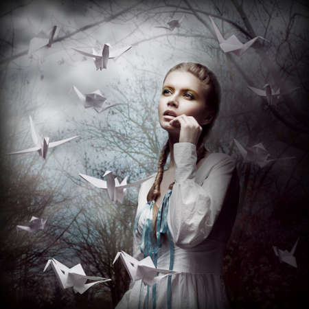 Inspiration. Woman with Flying White Origami Swans in Dark Mystic Forest photo