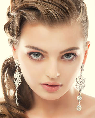 Jewelry. Portrait of Gorgeous Exquisite Woman with Shiny Earrings. Refinement photo