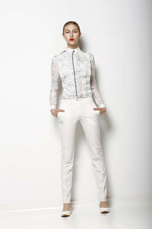 High Fashion. Trendy Woman in WHite Breeches in Graceful Pose. Spring Time Collection Stock Photo