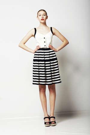falda: Mujer de moda en la falda de Stripped y camiseta de pie Colección Ropa Urbana