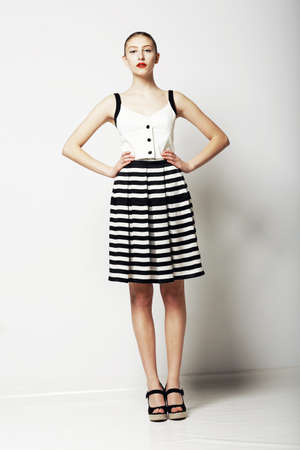nifty: Trendy Woman in Stripped Skirt and T-Shirt standing  Urban Clothing Collection