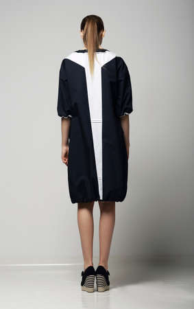 slicker: Rear View of of Trendy Chichi Woman in White-Black Contrast Raincoat. Vogue