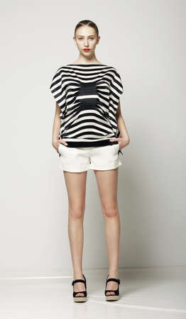 Full Length of Trendy Woman in Shorts and Grey Striped Shirt. Casual Modern Collection photo