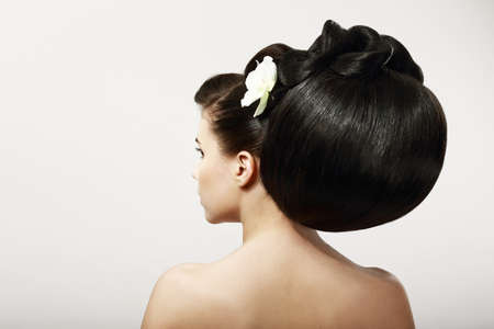 Haircare. Backside of Fashion Model with Creative Hairstyle. Smooth Healthy Black Hair with Flower. Spa Salon