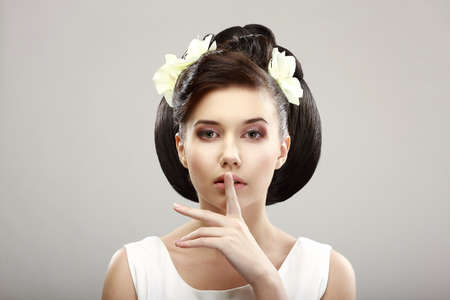 hist: Hush! Beautiful Young Woman showing Silence Sign with her Forefinger. Warning Stock Photo