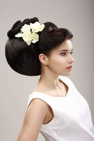 Charisma. Profile of Independent Woman with Futuristic Hairstyle and Orchid Flowers photo