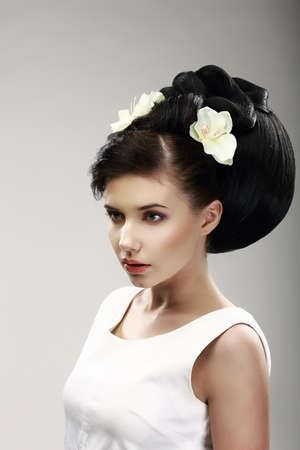floristry: Face of Beautiful Brunette Bride Fashion Model. Elegant Hairdo with Vernal Flowers Stock Photo