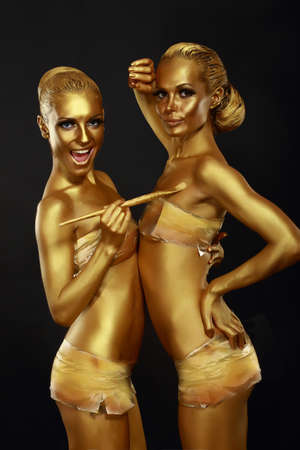 bodypaint: Fancy Dress Party. Couple of Women with Golden Metallic Painted Skin. Creativity Stock Photo