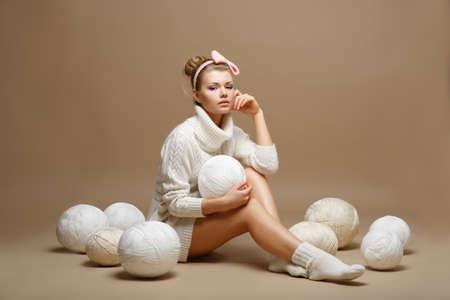 tejido de lana: Tareas del hogar. Mujer joven en blanco Tricot con bolas de lana. Costurera
