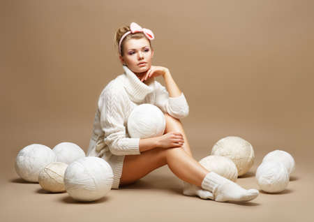 Embroidery. Woman in sitting White Cotton Knitwear with Heap Balls of Yarn photo