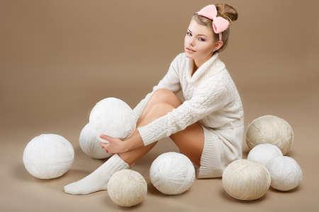 Crochet. Beautiful Needlewoman Sitting with Pile of White Skeins of Yarn. Needlecraft