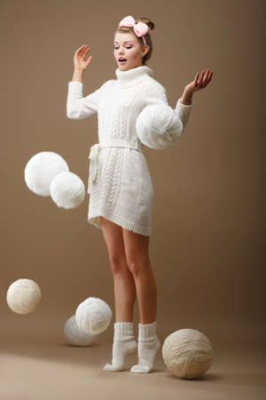 tricot: Falling Skeins  Surprised Woman in Woolen Knitted Jersey with White Balls of Yarn