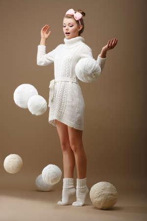 tejidos de punto: Madejas ca�da sorprendi� a la mujer en Jersey de punto de lana con bolas blancas de hilo Foto de archivo