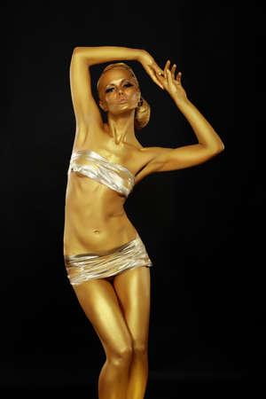 body paint: Brillante belleza Hermosa mujer delgada con la piel de oro posando Bodyart
