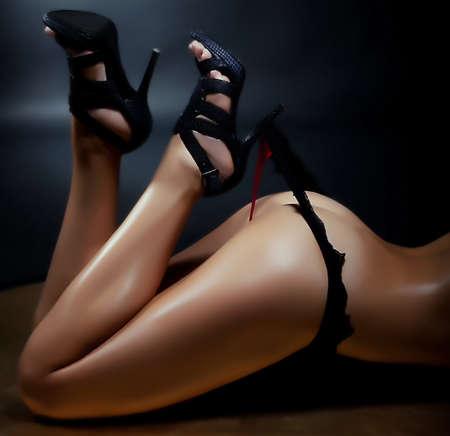 mujeres eroticas: Aspiraci�n mujer atractiva que tira de su tanga negro con tac�n Brillante Cuerpo Dorado Foto de archivo