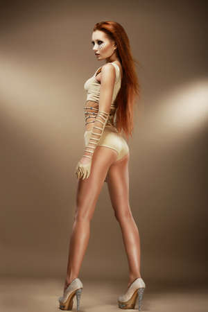 Nightlife  Performance  Sexy Red Hair Woman in Beige Stage Costume photo
