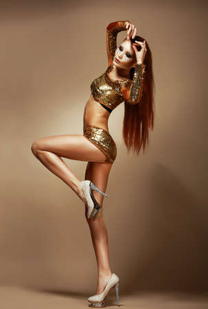 Dance  Nightclub  Gorgeous Redhead Woman in Golden Shorts  Fancy Dress Party photo
