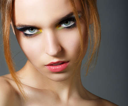 Magnetism. Character. Face of Young Red Hair Beauty with Colorful Eye Makeup photo
