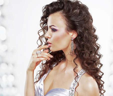 attractiveness: Mujer elegante con clase con joyas - anillo de platino y pendientes. Crespo Peinado Foto de archivo