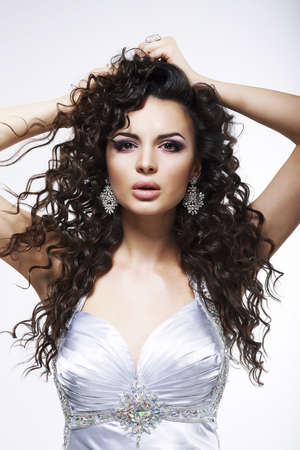 Sophistication. Fashionable Woman with Frizzy Hair with Earrings. Curly Hairstyle photo