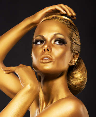 glowing skin: Reflexion  Portrait of Glossy Woman with Bright Golden Makeup  Bronze Bodypaint