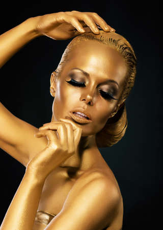 faceart: Glint  Coloring  Mysterious Woman with Golden Faceart  Creative Concept Stock Photo
