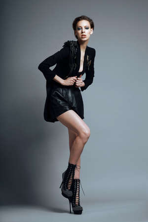 Vogue Style. Stylish Woman Fashion Model  in Trendy Black Clothes and Boots. Personality photo