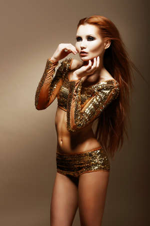 Radiance. Glitter. Glamorous Asian Woman in Golden Clubwear Stock Photo