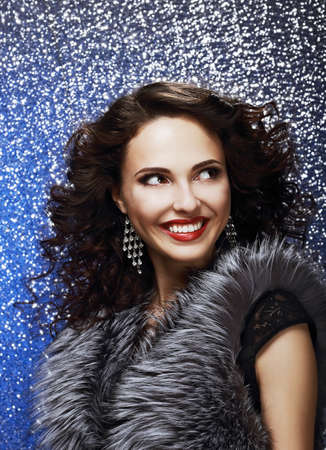 Sparkle  Beautiful Fashion Model with Shiny Earrings in Fur Vest  Toothy Smile photo