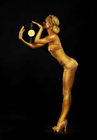 dorado: Futurismo. Bien proporcionado DJ Mujer de oro con disco de vinilo. Body Painting