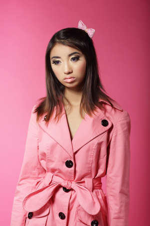 outwear: Stylish Japanese Girl in Pink Outwear over Colored Background