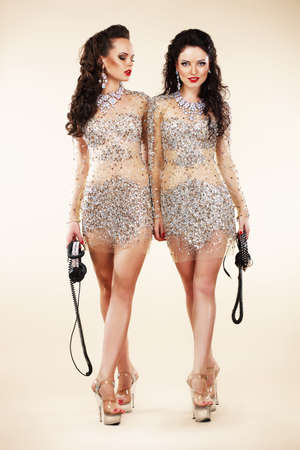 Luxury  Two Trendy Women Walking in Shiny Bright Dresses photo