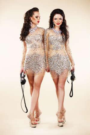 sexy headphones: Luxury  Two Trendy Women Walking in Shiny Bright Dresses