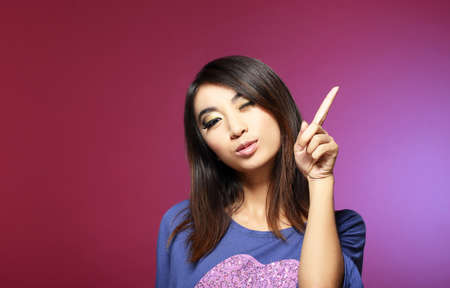 denote: Sale Concept  Friendly Young Saleswoman Pointing with Her Index Finger Upwards Stock Photo