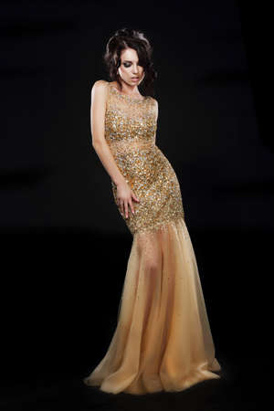 black dress: Vogue. Beautiful Fashion Model In Golden-Yellow Dress over Black Stock Photo