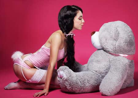 pantimedias: Mujer juguetona atractiva en ropa interior rosada con el oso de peluche Foto de archivo