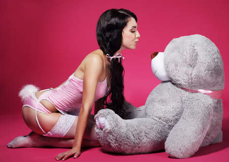 provocative woman: Seductive Playful Woman in Pink Lingerie with Teddy Bear