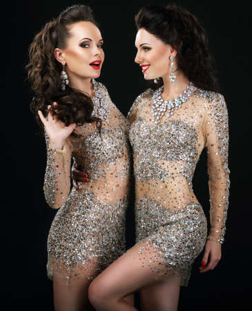 Excited Glamorous Couple in Platinum Dresses Talking photo