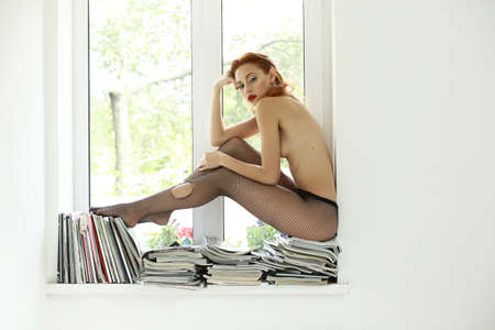 Naked Auburn Woman in Torn Tights on Magazines over Window Sitting photo