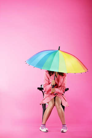 red umbrella: Vogue. Woman in Pink Coat sitting with Colorful Umbrella
